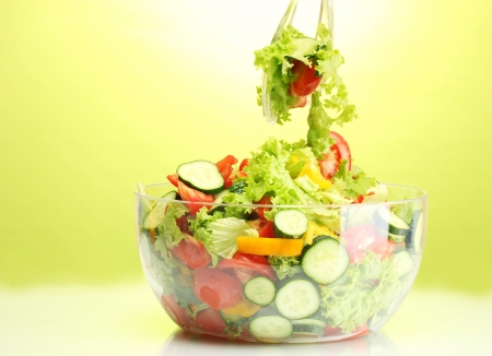 hinder: fresh vegetable salad in transparent bowl with spoon and fork on green background
