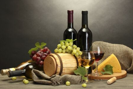 barrel, bottles and glasses of wine, cheese and ripe grapes on wooden table on grey background Stock Photo - 14455529