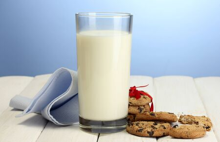 glass of milk and chocolate chips cookies with red ribbon on wooden table on blue background photo