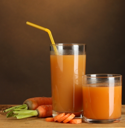 glasses of carrot juice on wooden table on brown background photo