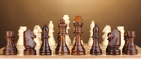 Chess board with chess pieces on brown background photo
