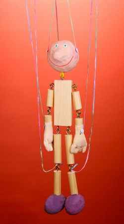 Wooden puppet on red background photo