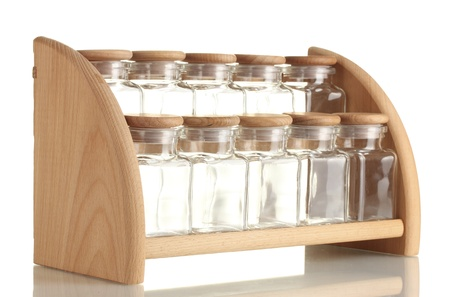 empty glass jars for spices on wooden shelf isolated on white photo