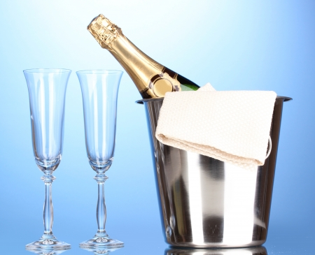 Champagne bottle in bucket with ice and glasses on blue background  photo