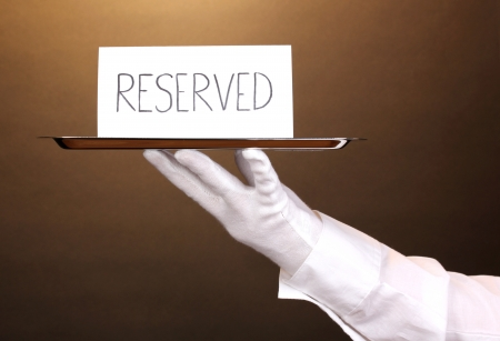 reserved: Hand in glove holding silver tray with card saying reserved on brown background