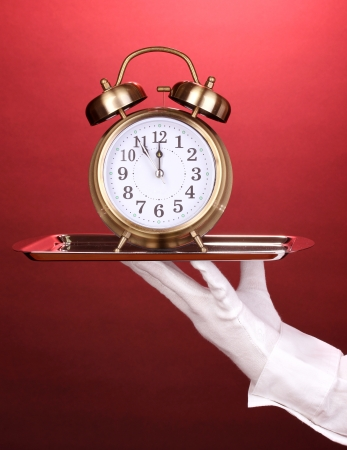 Hand in glove holding silver tray with alarm clock on red background photo