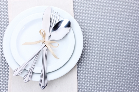kitchen restaurant: White empty plates with fork, spoon and knife tied with a ribbon on a grey tablecloth