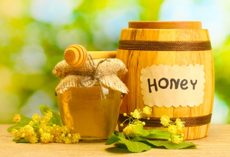 jar and barrel with linden honey and flowers on wooden table on green background Stock Photo - 14457663