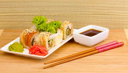 Tasty rolls served on white plate with chopsticks on wooden table on light background Stock Photo - 14457617