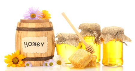 Sweet honey in jars and barrel with honeycomb, wooden drizzler and flowers isolated on white photo