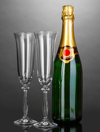Bottle of champagne and goblets on grey background photo