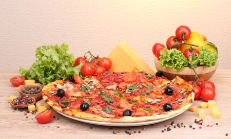 delicious pizza and vegetables on wooden table photo