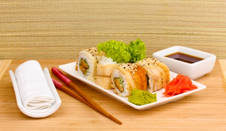 Tasty rolls served on white plate with chopsticks on wooden table on light background Stock Photo - 14469475