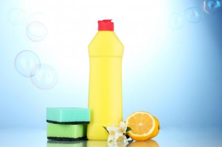Dishwashing liquid with sponges and lemon with flowers on blue background photo