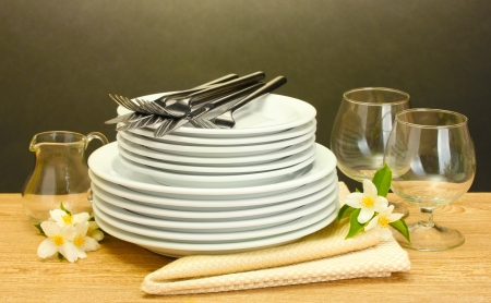 empty clean plates and glasses on wooden table on grey background photo