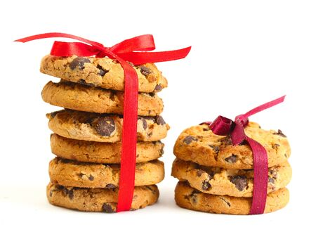 Chocolate chips cookies with red ribbons isolated on white  photo