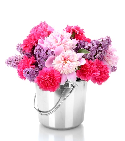 beautiful spring flowers in metal bucket isolated on white photo