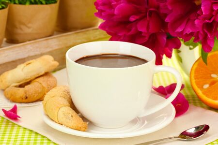 cup hot chocolate, cookies and flowers on table in cafe photo