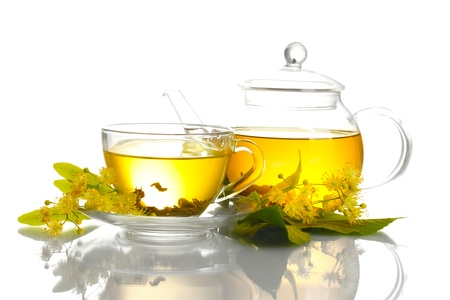 cup and teapot of linden tea and flowers isolated on white photo