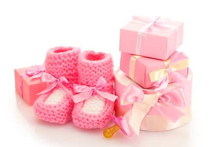 pink baby boots,  pacifier and gifts isolated on white photo