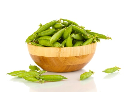 Green peas in wooden bowl isolated on white photo