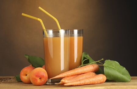 glasses of carrot and  apricot juice on wooden table on brown background photo