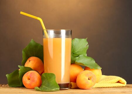 glass of apricot juice on wooden table on brown background photo