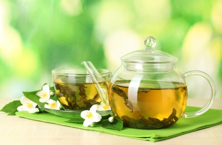green tea with jasmine in cup and teapot on wooden table on green background Stock Photo