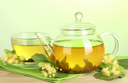 linden tea: teapot and cup with linden tea and flowers on wooden table on green background