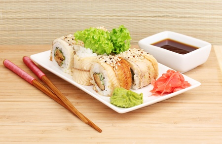 Tasty rolls served on white plate with chopsticks on wooden table on light background Stock Photo - 14519633