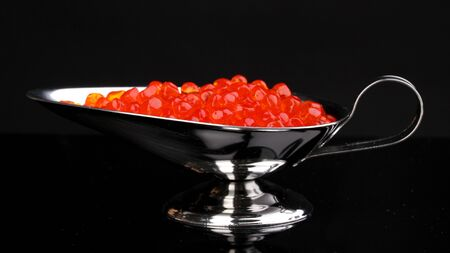 Red caviar in silver bowl isolated on black photo