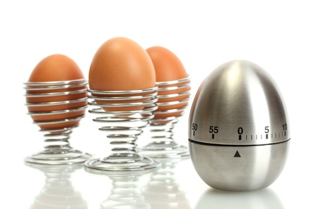 egg timer and egg in metal stand isolated on white Stock Photo - 14518349