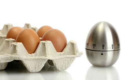 eggs in box and egg timer isolated on white photo