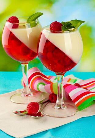 fruit jelly in glasses, berries and mint on table on green background photo