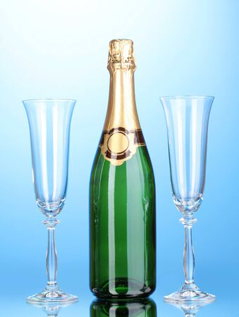 Bottle of champagne and goblets on blue background photo