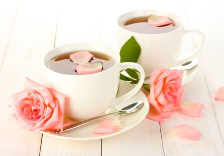 cups of tea with roses on white wooden table photo