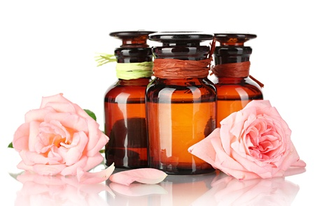 bottles of oil and roses isolated on white photo