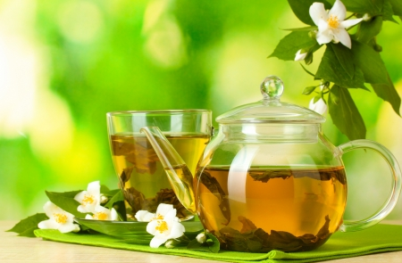 green tea with jasmine in cup and teapot on wooden table on green background Stockfoto