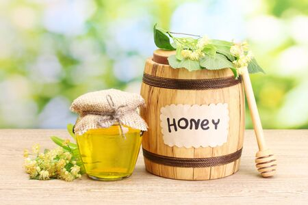 jar and barrel with linden honey and flowers on wooden table on green background Stock Photo - 14531856