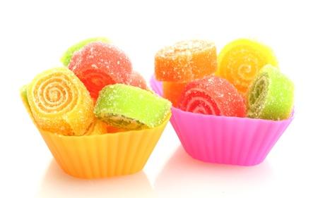 sweet jelly candies in cup cake cases isolated on white