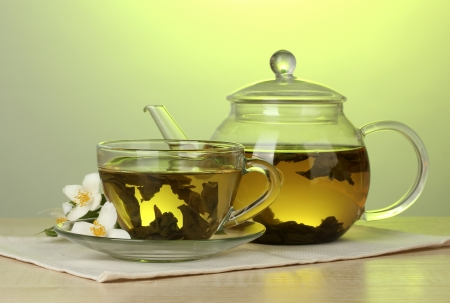 green tea with jasmine in cup and teapot on wooden table on green background photo