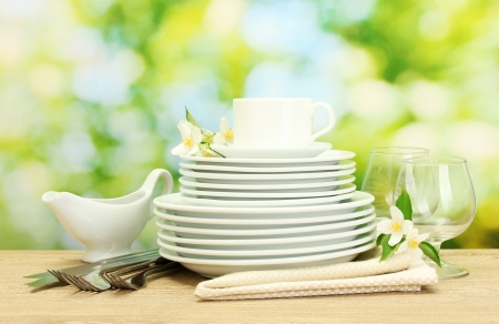 buffet table: empty clean plates, glasses and cup on wooden table on green background Stock Photo