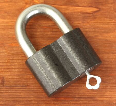 old padlock with key on wooden background close-up photo