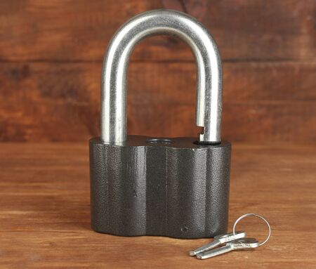 old padlock with keys on wooden background close-up photo