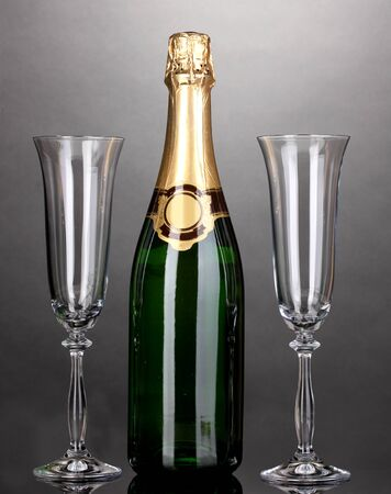 gold capped: Bottle of champagne and goblets on grey background Stock Photo