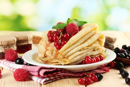 pancakes with berries, jam and honey on wooden table on  green background photo