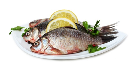 crucian carp: Fresh fishes with lemon and parsley on plate isolated on white