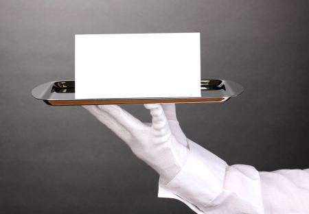 white gloves: Hand in glove holding silver tray with blank card on grey background