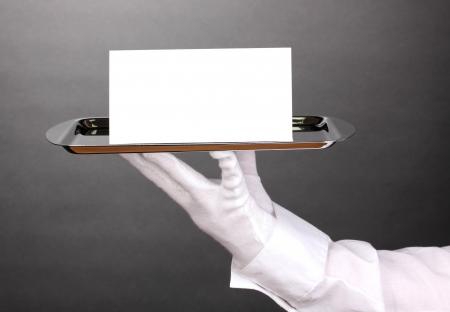 gant blanc: Main dans la main tenant plateau d'argent avec la carte vierge sur fond gris