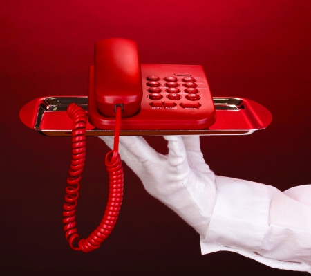 Hand in glove holding silver tray with telephone on red background photo